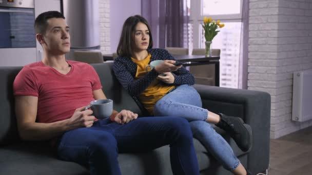 Mladý pár dohadovat o televizní kanály na pohovce