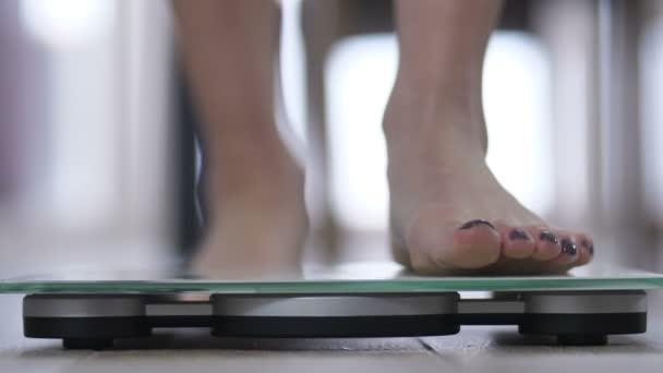 Zenske nohy stojící na tělesné hmotnosti váhy
