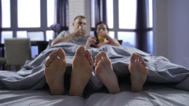 Piedi nudi di close-up di giovani coppie sotto coperta