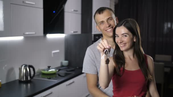 Portrait of couple shaking keys to new house