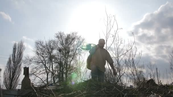 Man climbing the hill of garbage at dump site