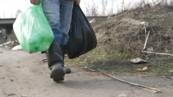 Male legs walking at garbage dump with trash bags