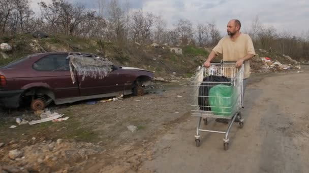 Homeless mature man pushing cart at garbage dump
