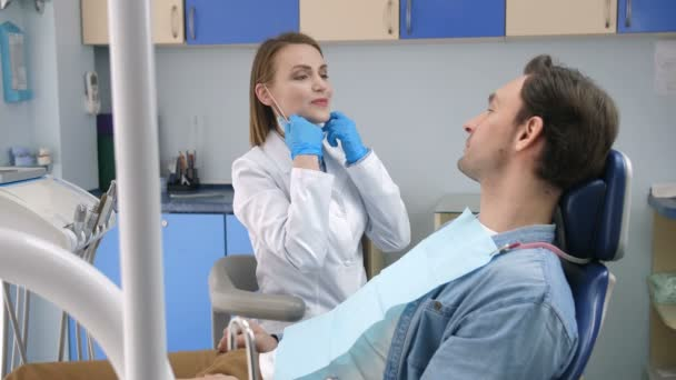 Female dentist starting check-up on male client