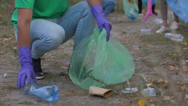 Ehrenamtliche lächeln in die Kamera, während sie Müll einsammeln