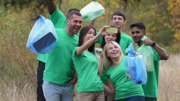 Smiling diverse volunteers taking selfie in forest