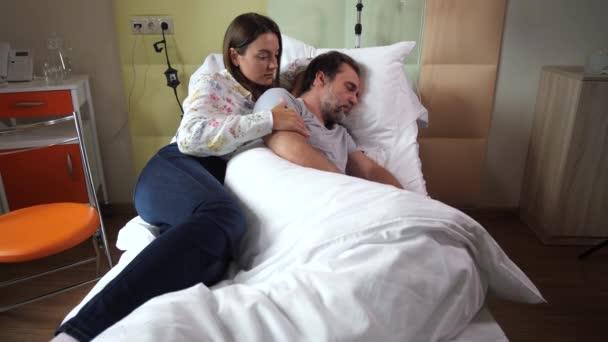 Milující smutná žena hladí manžela spí na klinice