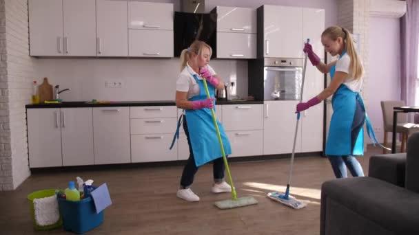 fröhliche Putzfrauen tanzen beim Bodenwischen