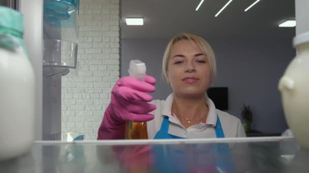 Žena čistič mycí lednice s čisticím prostředkem