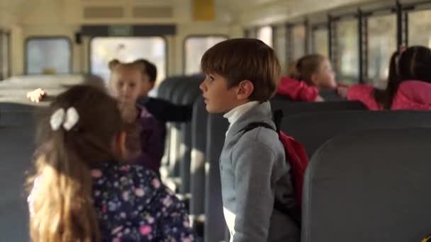 Aranyos iskolás fiú beszél lány osztálytársa a buszon