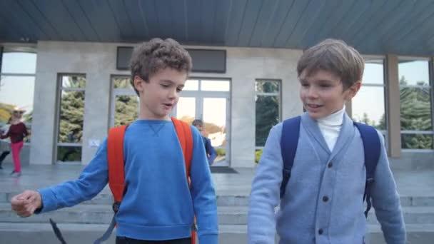 Aranyos iskolás fiúk beszélnek, miközben sétálnak az iskolából.