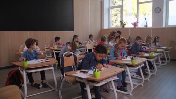 Különböző gyerekek rajzóra közben az iskolában