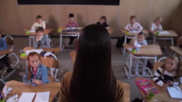 Tanár áll a diákok előtt az osztályteremben