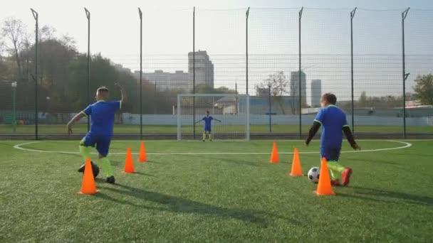 Junge Fußballer trainieren, um Tore zu schießen