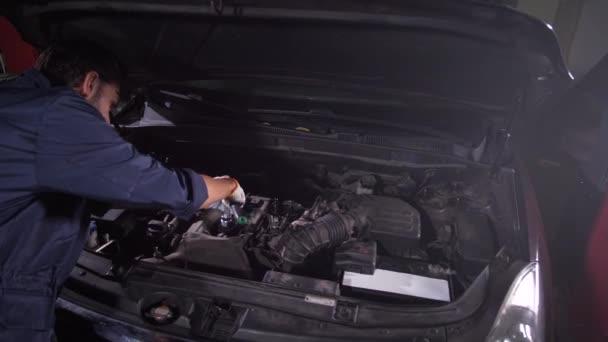 Opravář pomocí klíče při výměně olejového filtru
