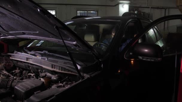 Auto mechanik se snaží nastartovat auto během opravy