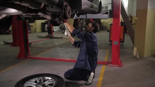 Specialista na opravy automobilů při kontrole podvozku