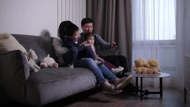 Přátelský asijské rodina sledování televize v obývacím pokoji
