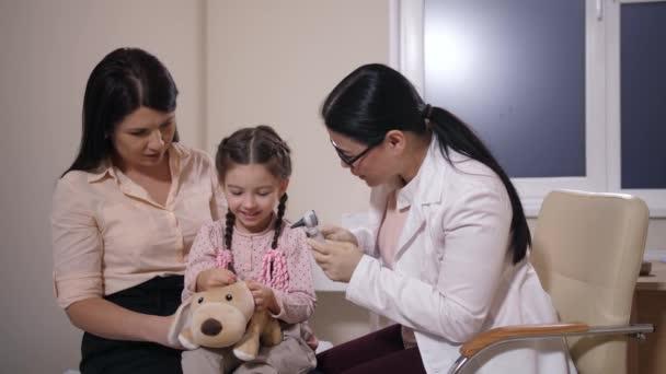 Arzt untersucht Ohr von Hund und Kind