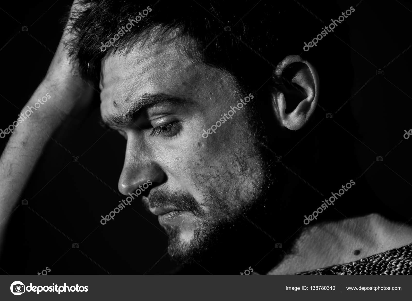 Sad young man on a dark background sad emotions black and white photography close up photo by puhimec