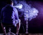 ein Mann raucht eine Wasserpfeife auf schwarzem Hintergrund, schöne Beleuchtung