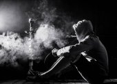Fotografie ein Mann raucht Shisha auf einem schwarzen Hintergrund, schöne Beleuchtung