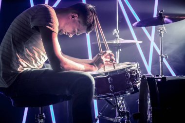 pensive man playing the drums. Against the background of colored