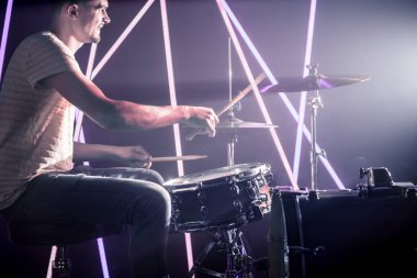 the man plays the drums.
