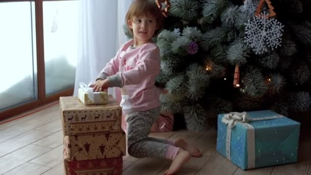 Kleine Kinder freuen sich über Geschenke im Weihnachtsbaum