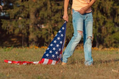 Woman with a flag of United States of America in the hand, outdoors, soft focus background