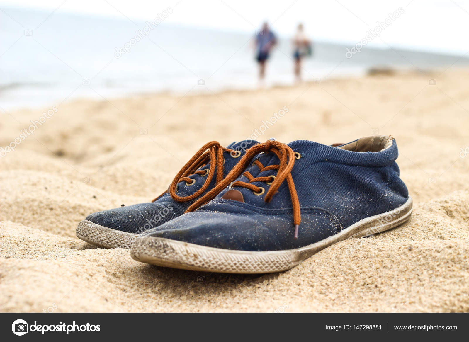 ca91dc6c84033d Simple blue men shoes with brown laces on sand on beach. Two people walking  in the background — Photo by ...