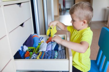 The child puts his clothes on. The boy pulls the T-shirt out of