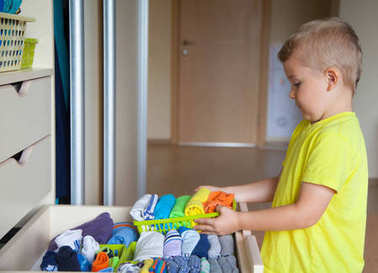 The child helps my mother. The boy puts the T-shirts in a drawer