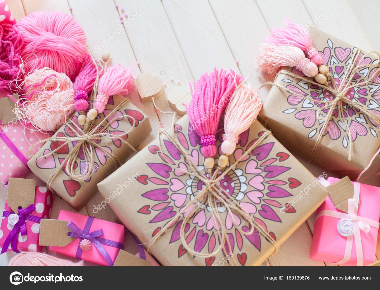 Pink tassels. Background of white wood. Women\'s handicrafts. The ...