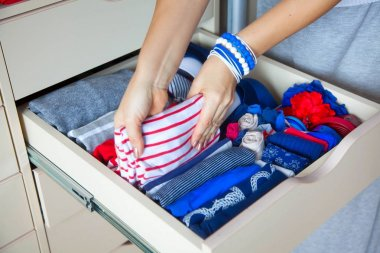Neatly folded clothes with accessories in chest of drawers. Mari