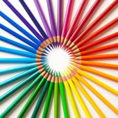 Pastelky - barevná tužka volně uspořádaná na bílém pozadí. Kulatý rám.