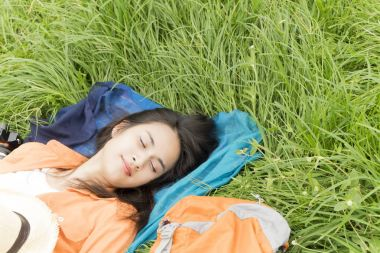 young woman lying on green grass enjoy the music with Headphones