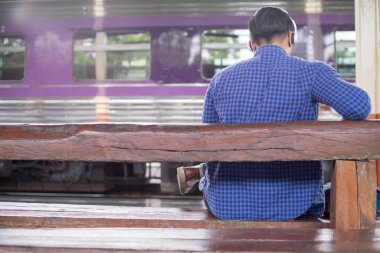 Man traveler with backpacker listening to music at trainstation