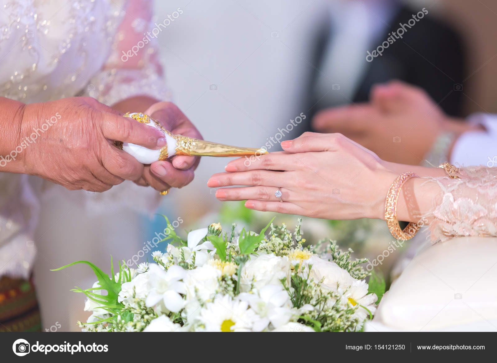Thai wedding hand of a bride receiving holy water from elders with ...