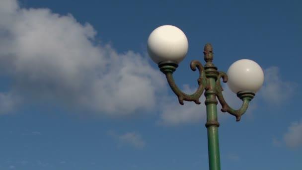 Bílá oblaka spěchat přes starou lampu na Santorini,