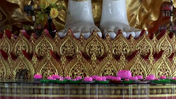 Svíčky hoří na úpatí obří sochy v Dhammikarama chrámu