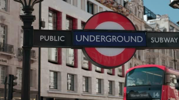 Enge Schuss von der Londoner U-Bahn Schild am Piccadilly Circus als mehrere rote Doppeldecker-Busse vorbeifahren im defokussierten Hintergrund
