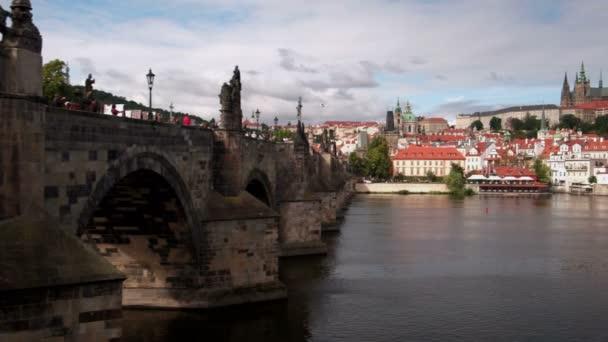 Pan z Karlova mostu na Pražský hrad s řeky Vltavy v popředí
