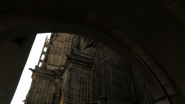 Camera walks through arch and tilted up to reveal south tower of St Vitus Cathedral, Prague