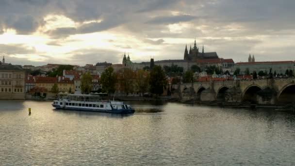Výletní loď otočí na řece Vltavě v Praze při západu slunce. Karlův most a Pražský hrad jsou v záběru