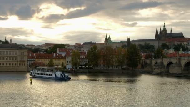 Pan z turistických lodí na Karlův most a Pražský hrad v západu slunce