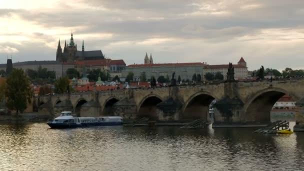 Pomalé posouvání přes Karlův most od Pražského hradu v podvečer jako turistická loď prochází pod