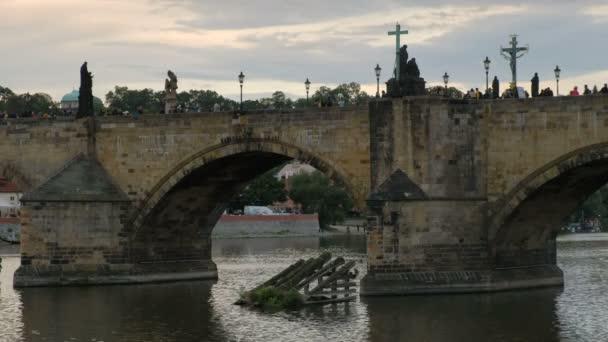Zavřete statický záběr turistů, přes Karlův most v Praze v září večer