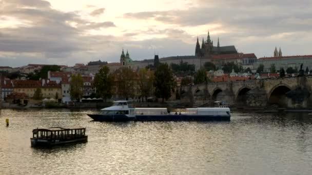 Široký záběr na turistické lodi na řece Vltavě v Praze při západu slunce. Karlův most a Pražský hrad jsou v záběru