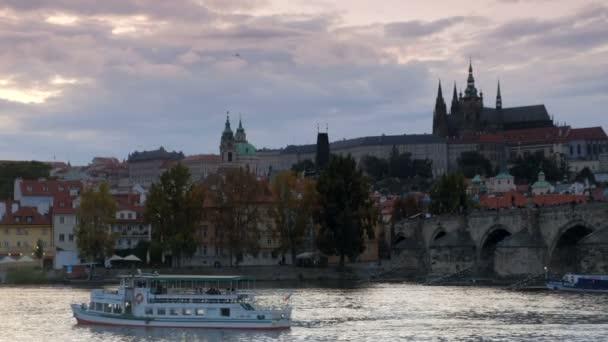 Posun od turistických lodí na Karlův most a Pražský hrad v podvečer